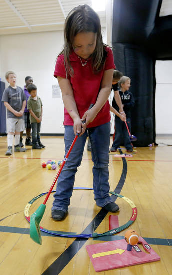 At right: Gabby Trinidad, 6, learns to golf during YMCA Healthy Kids Day at the Northside YMCA.