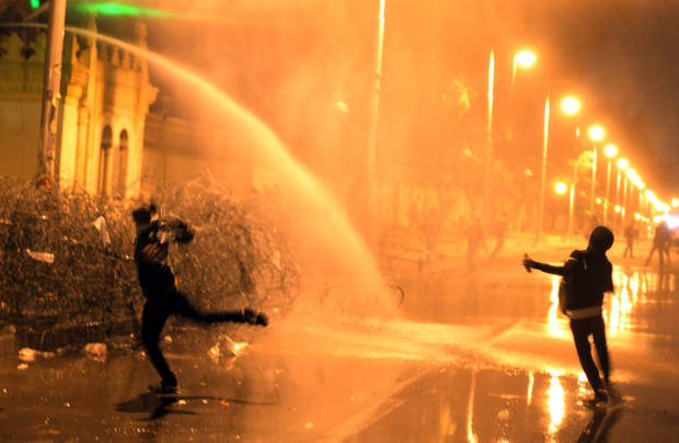 Egyptian protesters throw stones while security police open water cannons on them from inside the grounds of the presidential palace during a demonstration in Cairo, Egypt, Monday, Feb. 11, 2013. Security forces sprayed protesters with water hoses and tear gas outside the presidential palace Monday as Egyptians marked the second anniversary of autocrat Hosni Mubarak�s ouster with angry demonstrations against his elected successor.(AP Photo/Khalil Hamra)