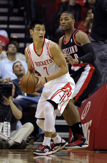Houston Rockets point guard Jeremy Lin (7) looks to pass the ball around Portland Trail Blazers point guard Damian Lillard (0) in the first half of an NBA basketball game on Saturday, Nov. 3, 2012, in Houston. (AP Photo/Pat Sullivan)