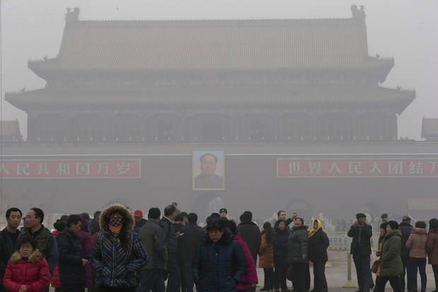 Visitors stand on Tiananmen Square across from a portrait of former Chinese leader Mao Zedong in thick haze in Beijing Tuesday, Jan. 29, 2013. Extremely high pollution levels shrouded eastern China for the second time in about two weeks Tuesday, forcing airlines in Beijing and elsewhere to cancel flights because of poor visibility and prompting government warnings for residents to stay indoors. (AP Photo/Ng Han Guan)