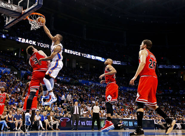 Oklahoma City's Russell Westbrook (0) dunks over Chicago's Omer Asik (3) during the NBA basketball game between the Chicago Bulls and the Oklahoma City Thunder at Chesapeake Energy Arena in Oklahoma City, Sunday, April 1, 2012. Photo by Sarah Phipps, The Oklahoman