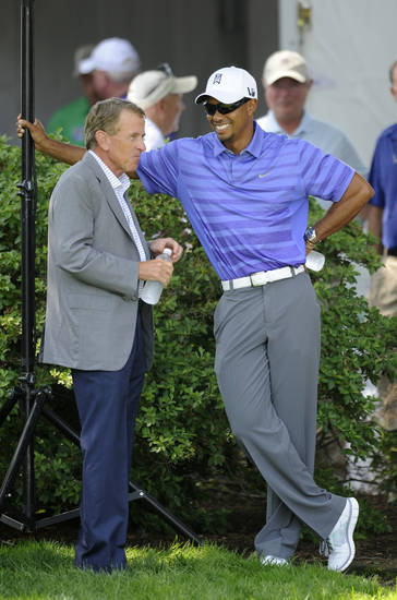 Tiger Woods, right, smiles as he stands next to PGA Tour Commissioner Tim Finchem, left, before an opening ceremony at the AT&T National Golf tournament, Wednesday, July 26, 2013, in Bethesda, Md. Woods will not play in the tournament because of a left elbow strain. (AP Photo/Nick Wass)
