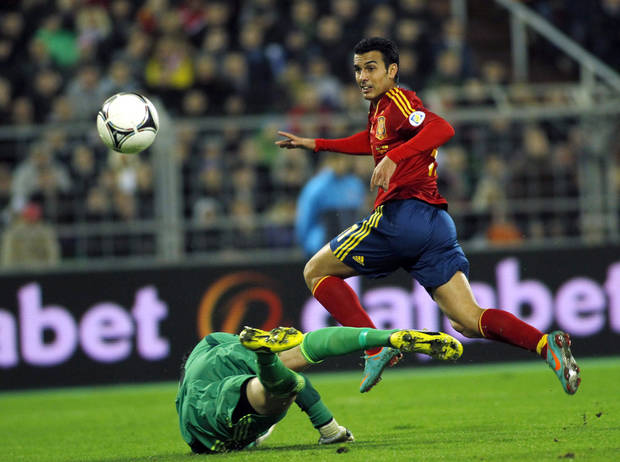 Spain's Pedro Rodriguez scores past Belarus' Sergei Veremko during a World Cup 2014 Group qualification match between Belarus and Spain national teams in Minsk, Belarus, on Friday, Oct. 12, 2012.(AP Photo/Sergei Grits)