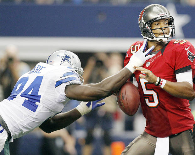 Dallas� DeMarcus Ware, left, strips the ball from Buccaneers quarterback Josh Freeman during the second half Sunday in Arlington, Texas. AP Photo