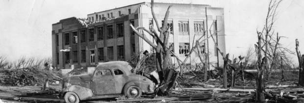 Bare tree limbs rise eerily as the damaged Woodward County courthouse stands in the background after a tornado  struck April 9, 1947.  The tornado killed 95 persons in Woodward, Okla. and covered parts of three states.