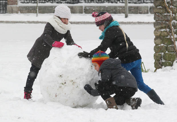 Children push a giant snowball in a park after heavy snowfall in Ghent, Belgium, Tuesday, Jan. 15, 2013. (AP Photo/Yves Logghe)