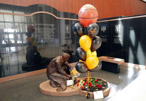 Flowers for OSU women's head coach Kurt Budke and assistant coach Miranda Serna lay on the Remember the 10 statue at Gallagher-Iba Arena in Stillwater, Okla.,  Friday, Nov. 18, 2011.  Photo by Sarah Phipps, The Oklahoman