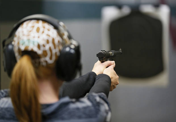 Tracy Lewis takes aim on a gun range Wednesday during a concealed-carry class at H&H Gun Range and Shooting Sports Complex. Photo by Nate Billings, The Oklahoman
