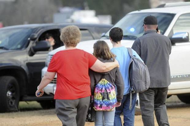 In this Tuesday, Jan. 29, 2013 photo, students and family leave the scene of the school bus shooting. Police, SWAT teams and negotiators were at a rural property where a man was believed to be holed up in a homemade bunker Wednesday, HAN 30, 2013 after fatally shooting the driver of a school bus and fleeing with a 6-year-old child passenger, authorities said. The man boarded the stopped school bus in the town of Midland City on Tuesday afternoon and shot the driver when he refused to let the child off the bus. The bus driver died. (AP Photo/The Dothan Eagle, Danny Tindell)