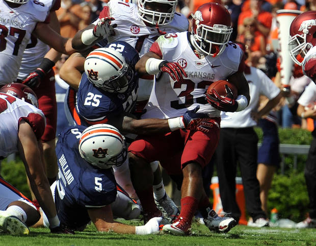 Arkansas's Dennis Johnson scores a touchdown against Auburn defenders Jake Holland (5) and Daren Bates (25) during the first half of an NCAA college football game on Saturday, Oct. 6, 2012 in Auburn, Ala.(AP Photo/Todd J. Van Emst)