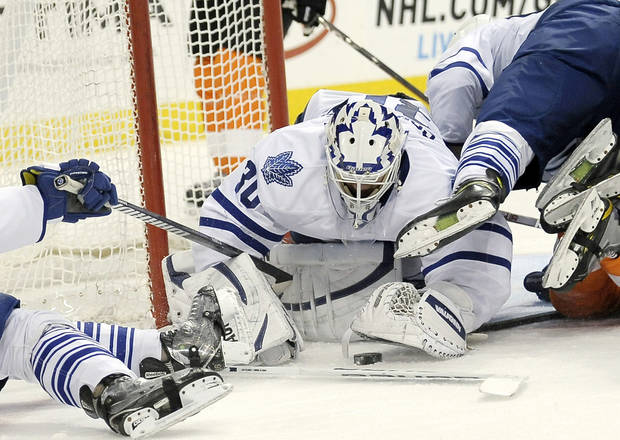 Toronto Maple Leafs&#039; Ben Scrivens (30) dives on a loose puck in front of the goal in the second period of an NHL hockey game against the Philadelphia Flyers on Monday, Feb 25, 2013, in Philadelphia. (AP Photo/Michael Perez)