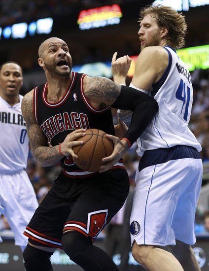 Chicago Bulls forward Carlos Boozer, center, is fouled by Dallas Mavericks forward Dirk Nowitzki (41), of Germany, under the net during the first half of an NBA basketball game, Saturday, March 30, 2013, in Dallas. Mavericks' Shawn Marion (0) is at left. (AP Photo/ Michael Mulvey)