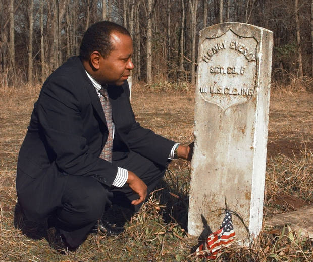 City of Langston�Historian Currie Ballard, at left, kneels beside a tombstone in Langston�s Beulahland Cemetery. �Langston takes its name from John Mercer Langston, a 19th-century black abolitionist, lawyer, politician and public speaker.  �The town and university have enjoyed disparate fortunes. The university is sparkling clean; it has its own entrance off the highway. The town has not prospered. Abandoned homes and businesses dot the streets.  � The town�s Beulahland Cemetery holds the graves of former slaves and Civil War soldiers.  Photo by Paul Hellstern,  The Oklahoman Archives