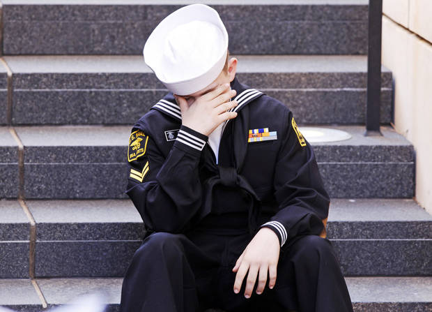 Zackary Kirkham, 13 of Sparks, Okla. and a member of the US Naval Sea Cadet Corp, covers his face as he sits on the steps while the names of the victims were read at the 19th anniversary Remembrance Ceremony at the Oklahoma City National Memorial Saturday morning, April 19, 2014, to honor the memory of the 168 victims killed in the 1995 bombing of the Murrah Federal Building. Photo by KT King, The Oklahoman