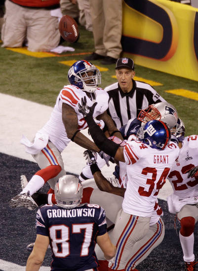 New York Giants players defend against a pass from New England Patriots quarterback Tom Brady during the second half of the NFL Super Bowl XLVI football game, Sunday, Feb. 5, 2012, in Indianapolis. The Giants won 21-17. (AP Photo/Charlie Riedel)  ORG XMIT: SB494