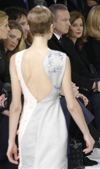 Valerie Trierweiler, right, companion of French President Francois Hollande, and Bernard Arnault, second right, head of French luxury brand LVMH, watch a model wearing a creation by Raf Simons for Christian Dior Spring Summer 2013 Haute Couture fashion collection, presented in Paris, Monday, Jan.21, 2013. (AP Photo/Christophe Ena)