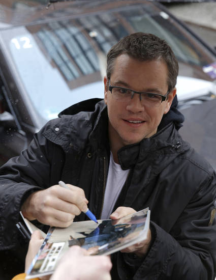 Actor Matt Damon signs autographs upon his arrival at the the photo call for the film Promised Land at the 63rd edition of the Berlinale, International Film Festival in Berlin, Friday, Feb. 8, 2013. (AP Photo/Gero Breloer)