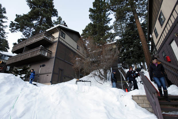 Members of the news media are shown outside a home, at left, in Big Bear, Calif., where two women were taken hostage by fugitive Christopher Dorner. Police scoured mountain peaks for days, using everything from bloodhounds to high-tech helicopters in their manhunt for Dorner, a revenge-seeking ex-cop. They had no idea he was hiding among them, possibly holed up in this vacation home across the street from their command post.     (AP Photo/Nick Ut)