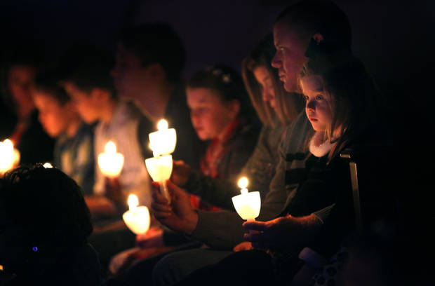 Brekyn Cope, 5, right, and her father, Brent Cope, hold a candle during the Christmas Candlelight Service at Crossings Community Church in Oklahoma City, Okla., Friday, Dec. 23, 2011. Photo by Sarah Phipps, The Oklahoman