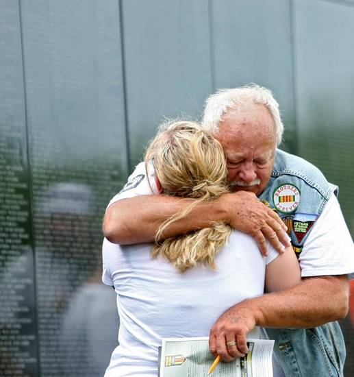 VIETNAM VETERANS: Veteran Paul Jones, of Guthrie, hugs his daughter Allison Robinson, after he looks up names on the Dignity Memorial Vietnam Wall at Reaves Park in Norman on Sunday, July 4, 2010. Photo by John Clanton, The Oklahoman ORG XMIT: KOD