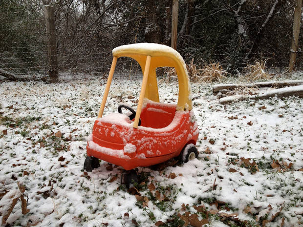 A toy car in a backyard in Edmond collects snow Friday morning December 28, 2012. Photo by Doug Hoke, The Oklahoman