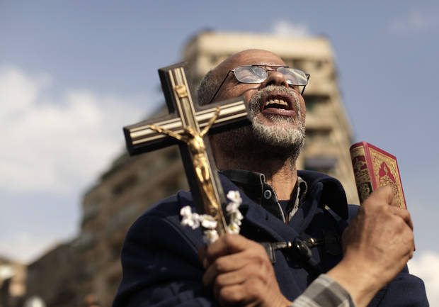 An Egyptian protester chants slogans and holds a cross and a Quran in Tahrir Square, Friday, Nov. 23, 2012. Supporters and opponents of Egypt's Islamist President Mohammed Morsi staged rival rallies Friday after he assumed sweeping new powers, a clear show of the deepening polarization plaguing the country. In a Thursday, Nov. 22, 2012 decree, Morsi put himself above the judiciary and also exempted the Islamist-dominated constituent assembly writing Egypt's new constitution from judicial review. (AP Photo/Maya Alleruzzo)