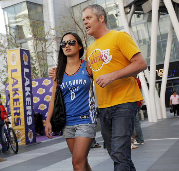 Thunder fan Alisa Le, left, and Lakers Jon Schimmer of San Diego walk through L.A. Live across from the Staples Center before Game 3 in the second round of the NBA basketball playoffs between the L.A. Lakers and the Oklahoma City Thunder at the Staples Center in Los Angeles, Friday, May 18, 2012. Le roots for the Thunder because Russell Westbrook attended UCLA. Photo by Nate Billings, The Oklahoman