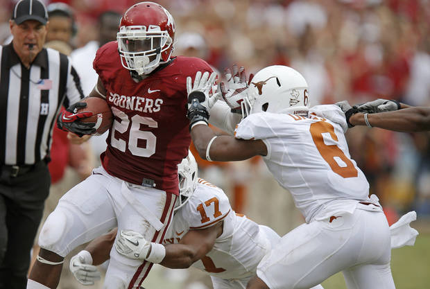 OU's Damien Williams (26) fights off UT's Adrian Phillips (17) and Quandre Diggs (6) during the Red River Rivalry college football game between the University of Oklahoma (OU) and the University of Texas (UT) at the Cotton Bowl in Dallas, Saturday, Oct. 13, 2012. Oklahoma won 63-21. Photo by Bryan Terry, The Oklahoman