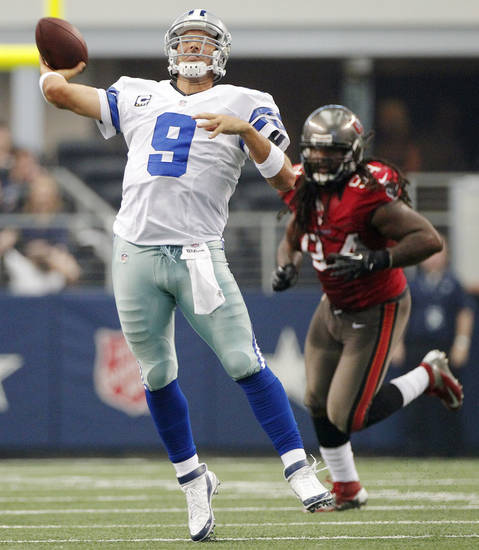 Dallas Cowboys quarterback Tony Romo (9) makes a long pass as Tampa Bay Buccaneers defensive end Adrian Clayborn (94) moves in during the second half of an NFL football game on Sunday, Sept. 23, 2012, in Arlington, Texas. (AP Photo/Tim Sharp)