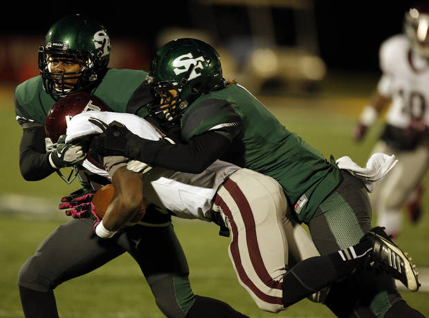 Santa Fe's Dhaniel Bly (13) and Phillip Sumpter (1) take down Memorial's Warren Wand (6) during a high school football game between Edmond Memorial and Edmond Santa Fe at Wantland Stadium in Edmond, Okla., Friday, Oct. 26, 2012.  Photo by Garett Fisbeck, The Oklahoman
