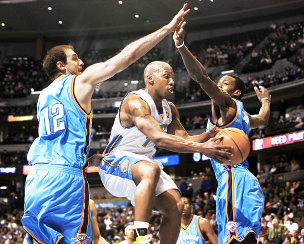 Nuggets guard Chauncey Billups, center, slips between Thunder center Nenad Krstic, left, and forward Jeff Green on Wednesday in Denver. AP Photo
