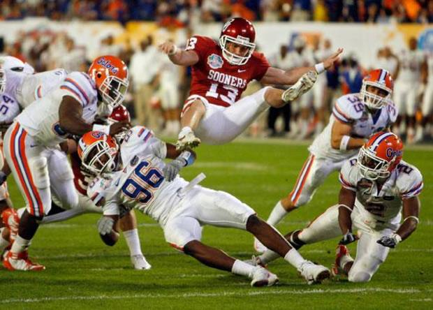 Oklahoma kicker Mike Knall (13) flies through the air after being hit by the Florida defense on a punt attempt during the second half of the BCS National Championship college football game between the University of Oklahoma Sooners (OU) and the University of Florida Gators (UF) on Thursday, Jan. 8, 2009, at Dolphin Stadium in Miami Gardens, Fla. Oklahoma lost the game 24-14 to the Gators.  PHOTO BY CHRIS LANDSBERGER, THE OKLAHOMAN