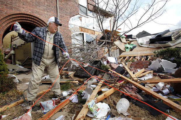 Bob Haslam works to clean up damage to his daughter's home in the Oak Tree addition on Wednesday, Feb. 11, 2009, after a tornado hit the area on Tuesday in Edmond, Okla.  PHOTO BY CHRIS LANDSBERGER, THE OKLAHOMAN