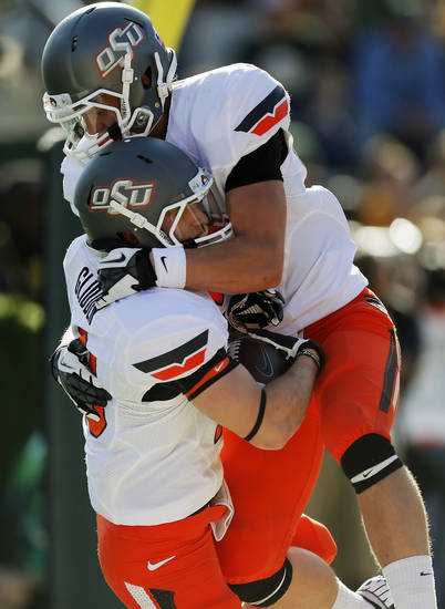 Oklahoma State's Blake Webb (85) leaps on David Glidden (13) after Glidden caught a touchdown pass in the fourth quarter during a college football game between the Oklahoma State University Cowboys (OSU) and the Baylor University Bears at Floyd Casey Stadium in Waco, Texas, Saturday, Dec. 1, 2012. Photo by Nate Billings, The Oklahoman