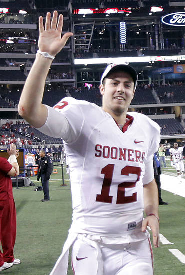 Oklahoma's Landry Jones (12) waves to fans as he runs off the field after the Sooners' 23-20 win over Nebraska during the Big 12 football championship game between the University of Oklahoma Sooners (OU) and the University of Nebraska Cornhuskers (NU) at Cowboys Stadium on Saturday, Dec. 4, 2010, in Arlington, Texas.  Photo by Chris Landsberger, The Oklahoman