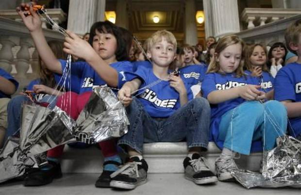 From left, Amanda Arroyo, Brady Moran, and Kiley O'Brien, first-graders at Cumberland Hills Elementary School, wrap up  G.I.  Joe figures that were launched with parachutes from the rotunda of the Rhode Island Statehouse in Providence, R.I., to open the 2010 International  G.I.  Joe Collectors' Convention, Friday, April 30, 2010. (AP Photo/Stew Milne)