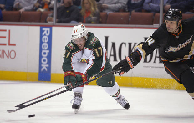 Minnesota Wild left wing Torrey Mitchell, left, and Anaheim Ducks defenseman Sheldon Souray reach for the puck during the first period of an NHL hockey game, Friday, Feb. 1, 2013, in Anaheim, Calif. (AP Photo/Mark J. Terrill)