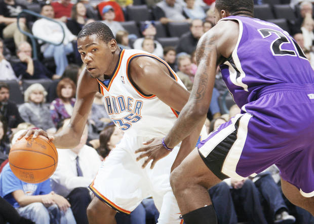 Oklahoma City's Kevin Durant, left, tries to dribble around Donte Greene of Sacramento during Thursday's game at the Ford Center. Photo by Nate Billings, The Oklahoman