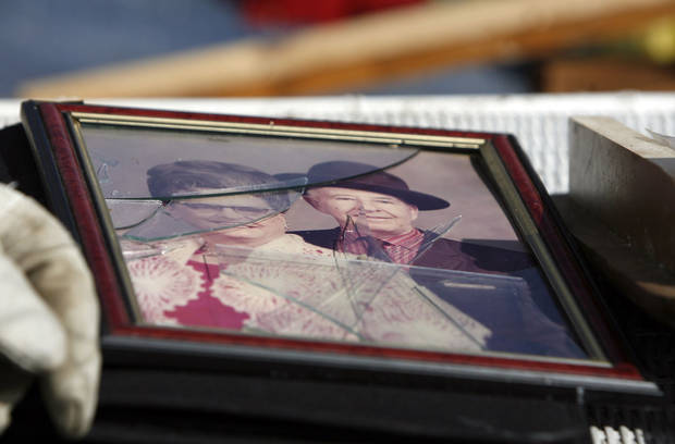 A family photo is rescued from a damaged home, Thursday, Feb. 12, 2009, in Lone Grove, Okla. PHOTO BY SARAH PHIPPS, THE OKLAHOMAN
