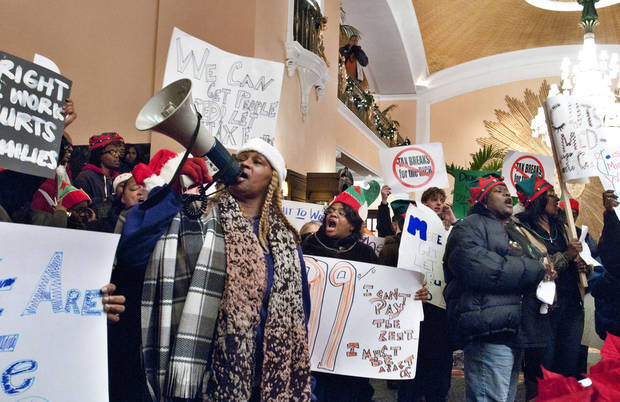 A group of demonstrators inside the Amway Grand Plaza Hotel call for Dick DeVos to end financial support for right-to-work legislation, Wednesday, Dec. 5, 2012 in Grand Rapids, Mich. (AP Photo/The Grand Rapids Press, Chris Clark) ALL LOCAL TV OUT; LOCAL TV INTERNET OUT