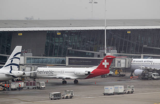 Baggage carts make their way past a Helvetic Airways aircraft from which millions' of dollars worth of diamonds were stolen on the tarmac of Brussels international airport, Tuesday, Feb. 19, 2013. Eight armed and masked men made a hole in a security fence at Brussels' international airport, drove onto the tarmac and snatched millions of dollars' worth of diamonds from the hold of a Swiss-bound plane without firing a shot, authorities said Tuesday. (AP Photo/Yves Logghe)