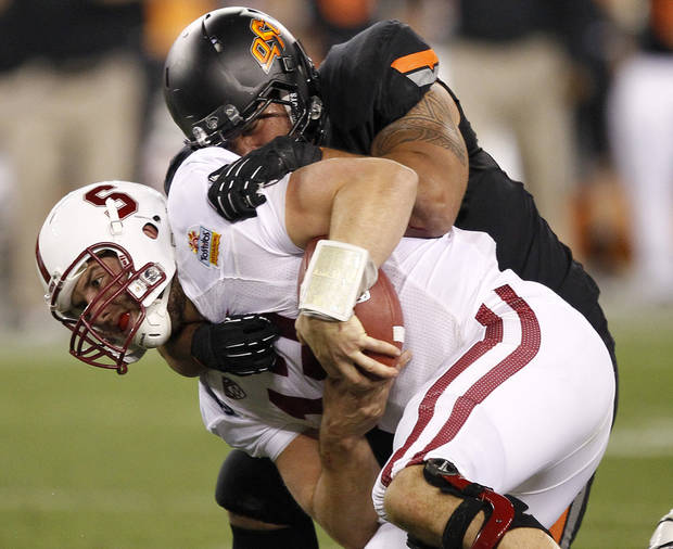 Stanford quarterback Andrew Luck, front, is sacked by Oklahoma State defensive end Jamie Blatnick during the second half of the Fiesta Bowl NCAA college football game Monday, Jan. 2, 2012, in Glendale, Ariz. (AP Photo/Matt York)