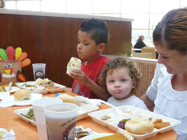 Kaden Martin, 7, Chaseon Mosby, 18 months, and Amanda Weible eat a holiday meal Thursday at Norman's  Community Thanksgiving Dinner. PHOTO BY CONNIE HEFNER, FOR THE OKLAHOMAN <strong>Connie Hefner</strong>