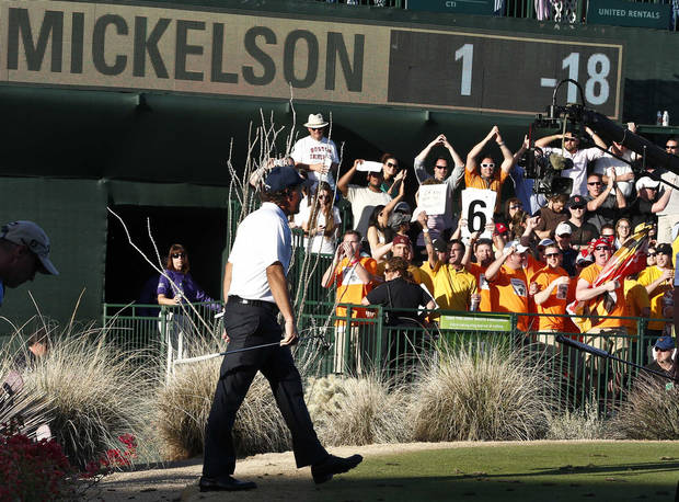 As the crowd cheers, Phil Mickelson walks to the 16th green during the second round of the Waste Management Phoenix Open golf tournament on Friday, Feb. 1, 2013, in Scottsdale, Ariz. (AP Photo/Ross D. Franklin)