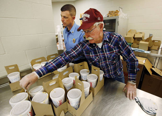 Fire Department Capt. Joel Chesser, left, and retired fireman Jerry Loeffelholz get to-go orders ready Thursday at the annual Police-Fire Chili Supper that raises money for the Cleveland County Christmas Store. PHOTO BY STEVE SISNEY, THE OKLAHOMAN <strong>STEVE SISNEY</strong>