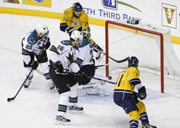 Nashville Predators center Colin Wilson (33) scores against San Jose Sharks goalie Antti Niemi (31), of Finland, in the overtime period to give the Predators a 1-0 win in an NHL hockey game Tuesday, Feb. 12, 2013, in Nashville, Tenn. Watching for the puck are Sharks defenseman Dan Boyle (22) and center Michal Handzus (26), of Slovakia, and Predators center David Legwand (11). (AP Photo/Mark Humphrey)