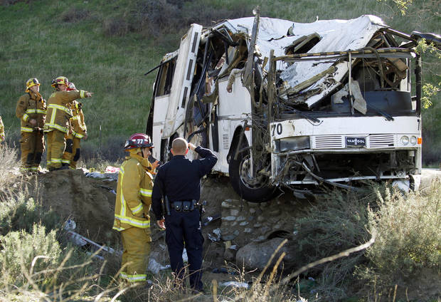 EDITORS NOTE GRAPHIC CONTENT - Firefighters and a California Highway Patrol officer survey the scene of an accident where at least eight people were killed and 38 people were injured after a tour bus, left, carrying a group from Tijuana, Mexico crashed with two other vehicles just north of Yucaipa, Calif., Sunday, Feb. 3, 2013. The arm of a deceased victim is seen at top center. (AP Photo/Reed Saxon)