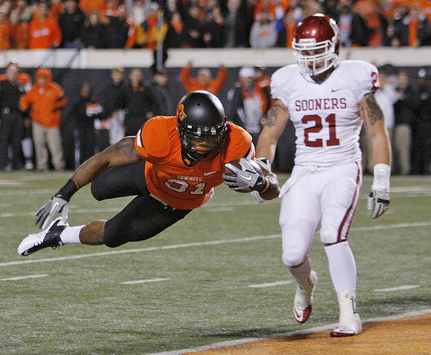 OSU's Jeremy Smith (31) flies into the end zone for a touchdown past OU's Tom Wort (21) in the first quarter during the Bedlam college football game between the Oklahoma State University Cowboys (OSU) and the University of Oklahoma Sooners (OU) at Boone Pickens Stadium in Stillwater, Okla., Saturday, Dec. 3, 2011. Photo by Nate Billings, The Oklahoman