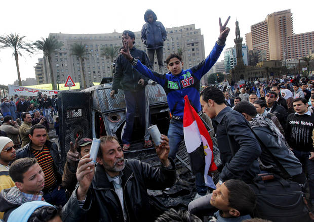 Egyptian protesters celebrate the capture of a state security armored vehicle that demonstrators commandeered during clashes with security forces and brought to Tahrir Square in Cairo, Egypt, Tuesday, Jan. 29, 2013. Egypt�s army chief warned Tuesday of the �the collapse of the state� if the political crisis roiling the nation for nearly a week continues, but said the armed forces will respect the right of Egyptians to protest. (AP Photo/Amr Nabil)