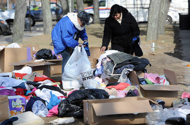 Two women look through piles of clothing in front of Long Beach city hall donated for victims of Superstorm Sandy on Tuesday, Nov 6, 2012, in Long Beach, N.Y. (AP Photo/Kathy Kmonicek) ORG XMIT: NYKK125